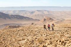 Trois randonneurs tenant la traînée de montagnes, désert du Néguev, Isra Photographie stock libre de droits