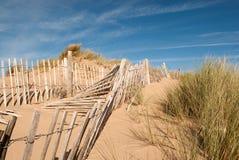 Trois rangées de barrière cassée sur des dunes de sable Photos stock