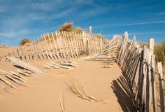 Trois rangées de barrière cassée sur large horizontal de dunes de sable Photos stock