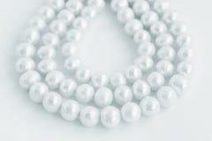 Trois rangées de collier de perle naturelle sur le blanc Photographie stock libre de droits