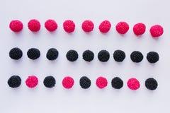 Trois rangées de gelée sous forme de framboises rouges et de bla noir Image libre de droits