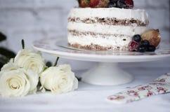 Trois roses blanches Gâteau de chocolat nu Defocused avec de la crème derrière Un fond rustique lumineux Foyer sélectif Photographie stock