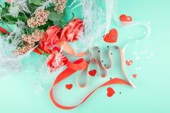 Trois roses de couleur de corail, sur un fond vert, sont décorées des rubans, des confettis et des coeurs rouges photographie stock