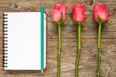 Trois roses et carnet vide Images stock