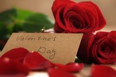 Trois roses rouges avec des pétales sur la table en bois et la carte de papier pour le jour de valentines Photographie stock