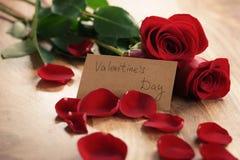 Trois roses rouges avec des pétales sur la table en bois et la carte de papier pour le jour de valentines Photos libres de droits