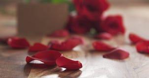 Trois roses rouges avec la carte de papier vide sur la vieille table en bois Photo stock