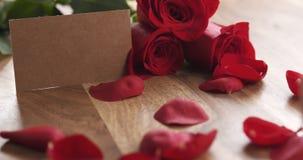 Trois roses rouges avec la carte de papier vide sur la vieille table en bois Images libres de droits