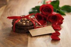 Trois roses rouges avec les biscuits faits maison de chocolat pour le jour de valentines Images stock
