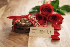 Trois roses rouges avec les biscuits faits maison de chocolat sur le vieux plan rapproché en bois de table Image stock