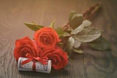Trois roses rouges et groupes de dollars Photo libre de droits