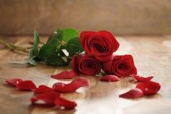 Trois roses rouges et pétales sur la vieille table en bois avec l'espace de copie Photographie stock libre de droits