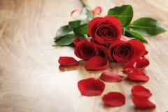 Trois roses rouges et pétales sur la vieille table en bois avec l'espace de copie Photos stock
