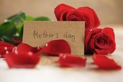 Trois roses rouges et pétales sur la vieille table en bois avec la carte de papier de jour de mères Images libres de droits