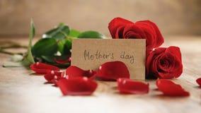 Trois roses rouges et pétales sur la vieille table en bois avec la carte de papier de jour de mères Photo libre de droits