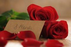 Trois roses rouges et pétales sur la vieille table en bois avec la carte de papier du 8 mars Image libre de droits