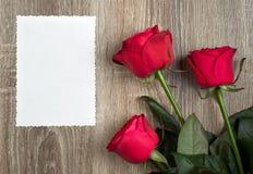 Trois roses rouges et page blanche sur le bois Images stock