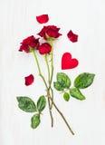 Trois roses rouges sur de longues tiges et coeur sur le bois blanc, carte d'amour Photo libre de droits
