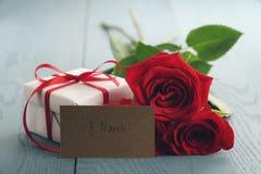 Trois roses rouges sur la table en bois bleue avec la carte de papier de cadeau et du 8 mars Photo stock