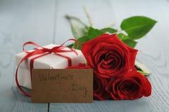 Trois roses rouges sur la table en bois bleue avec la carte de papier de jour de cadeau et de valentines Image stock