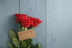 Trois roses rouges sur la table en bois bleue avec la carte de papier de jour de valentines Photographie stock