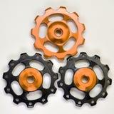 Trois rouleaux de couleur, vitesses noires et d'or pour le dérailleur arrière de bicyclette sur un fond blanc photos stock