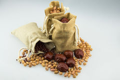 Trois sacs à toile de jute, ont été remplis d'arachides, de dates rouges et de haricots rouges Photographie stock libre de droits