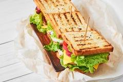 Trois sandwichs avec du jambon, la laitue et les légumes frais d'un plat, fin  images libres de droits