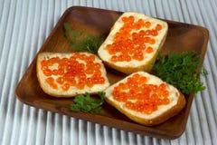 Trois sandwichs avec le caviar rouge du plat en bois Images libres de droits