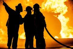 Trois sapeurs-pompiers combattant un feu brûlant photographie stock libre de droits