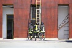trois sapeurs-pompiers dans les sapeurs-pompiers images stock