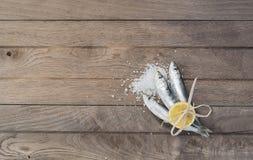 Trois sardines enveloppées avec le citron sur la table en bois Photographie stock libre de droits