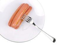 Trois saucisses de francfort délicieuses d'un plat blanc images stock
