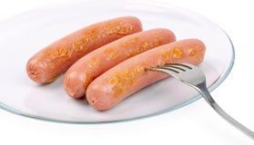 Trois saucisses de francfort délicieuses d'un plat blanc photographie stock libre de droits