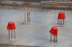 Trois seaux rouges couvrant les barres de renforcement sur une construction SI photos stock