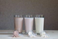 Trois secousses de protéine de lactalbumine de lait dans des tasses en verre sont arrangées dans une rangée avec trois scoops de  photos libres de droits
