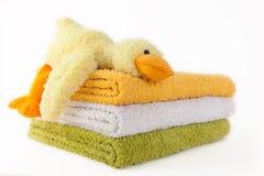 Trois serviettes colorées avec le canard jaune de peluche Photographie stock