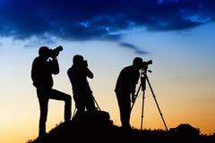 Trois silhouettes d'homme photographiant le ciel Photo stock