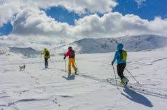 Trois skieurs et leur chien suivant leur manière Photographie stock libre de droits