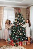 Trois soeurs décorent l'arbre de Noël Images stock