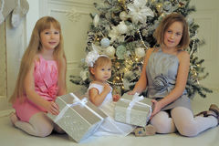 Trois soeurs de filles s'asseyant à l'arbre de Noël Image stock