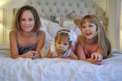 Trois soeurs de filles se trouvant ensemble sur un lit Images stock