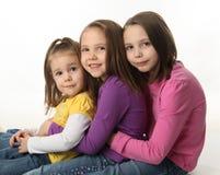 Trois soeurs s'asseyant vers le bas s'étreignant Image libre de droits