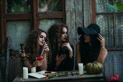 Trois sorcières de vintage effectuent le rituel magique Photos stock