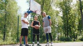 Trois sportifs beaux restant sur l'extérieur de terrain de basket - homme dans l'uniforme noir tenant la boule banque de vidéos