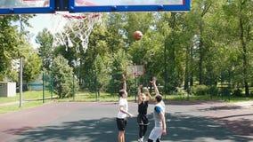 Trois sportifs jouant au basket-ball sur l'extérieur de cour - homme dans l'uniforme noir jetant la boule et le marquage banque de vidéos