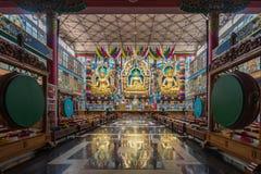 Trois statues d'or à l'intérieur de Vihara au bouddhiste Monast de Namdroling Photos libres de droits