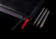 Trois stylos près du carnet sur un fond noir Images stock