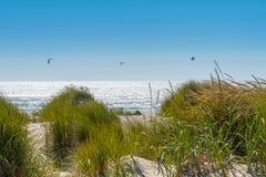 Trois surfers de cerf-volant au-dessus des dunes herbeuses Image libre de droits