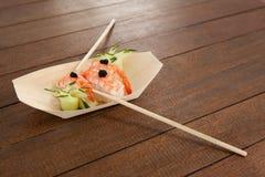 Trois sushi de nigiri ont servi avec des baguettes dans le plat en bois de bateau Photo libre de droits
